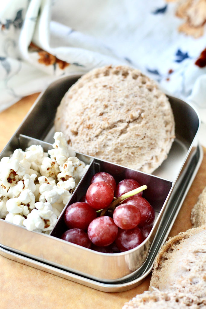 homemade uncrustable popcorn and red grapes in stainless steel bento box